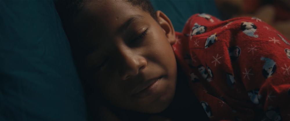 Young Adam sleeps peacefully in his Christmas pyjamas